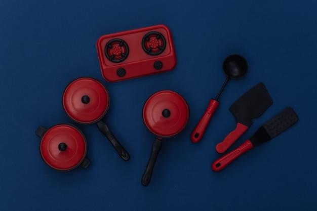 Игрушка кухонная утварь и инструмент на классическом синем фоне. цвет 2020. вид сверху
