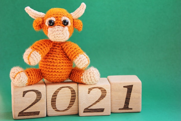 A toy knitted bull is located the wooden blocks with the numbers 2021 on them on a green