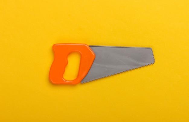 黄色の背景におもちゃのミニプラスチックのこぎり。上面図