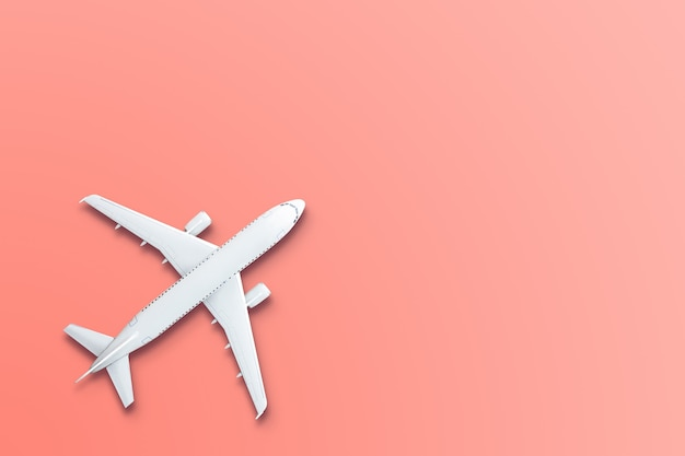 Toy model airplane design miniature on bight living coral background. the idea of tickets for the trip, traveling by plane, new discoveries, summer holidays.