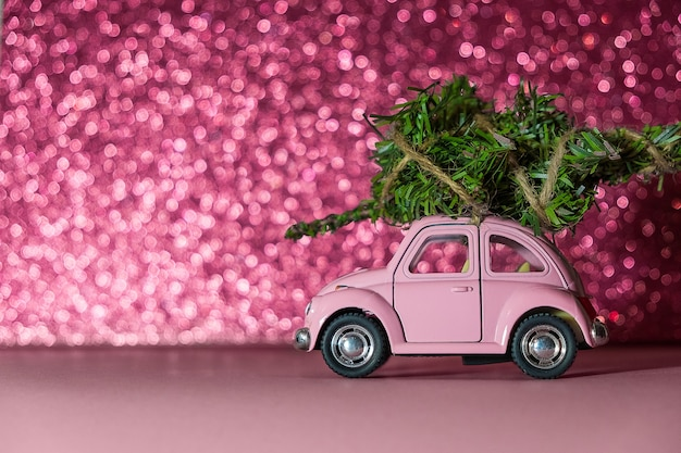 Toy model car with christmas tree on on the roof rides on pink blurred glitter background