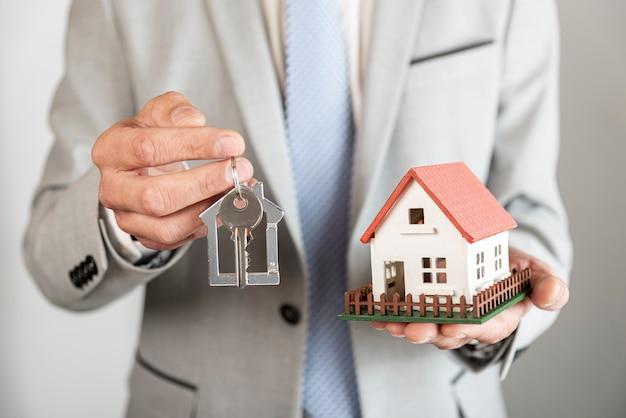 Дом модели игрушек и ключи в руках делового человека