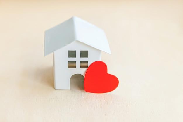 나무 배경에 붉은 마음으로 장난감 모델 하우스. 에코 빌리지, 추상적 인 환경 배경