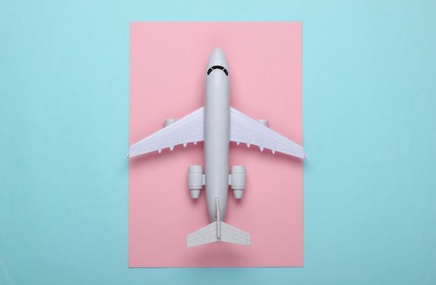青ピンクのパステルカラーの旅客機のおもちゃモデル。観光、空の旅、ミニマリズムの概念。