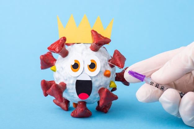 Игрушечная модель коронавируса с испуганным лицом - круглыми глазами и открытым ртом в ожидании инъекции