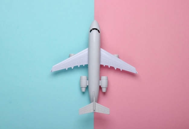 Toy model of a passenger plane on a blue-pink pastel. the concept of tourism, air travel, minimalism.