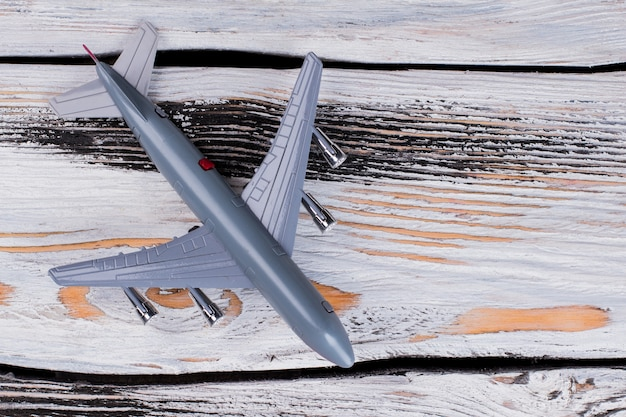 Toy model of passenger plane on wooden table. close up top view flat lay.