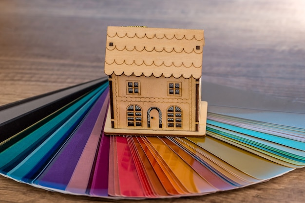 Toy model of wooden house on colour swatch
