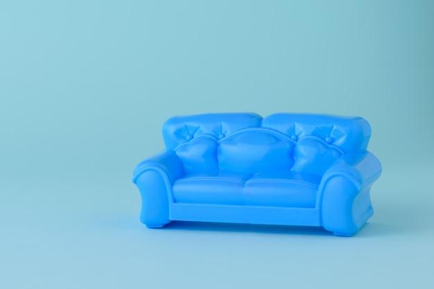 Игрушка современный синий красивый диван на синем фоне. образец красивой мебели для дома. минималистский.