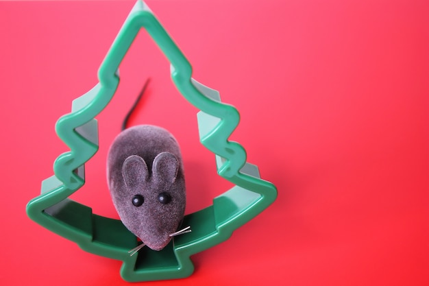 Toy mouse and a christmas tree on a red background