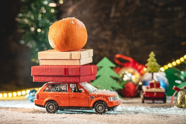 A toy orange car is carrying a christmas gifts
