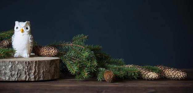 モミの枝で切った木の上のおもちゃのフクロウ