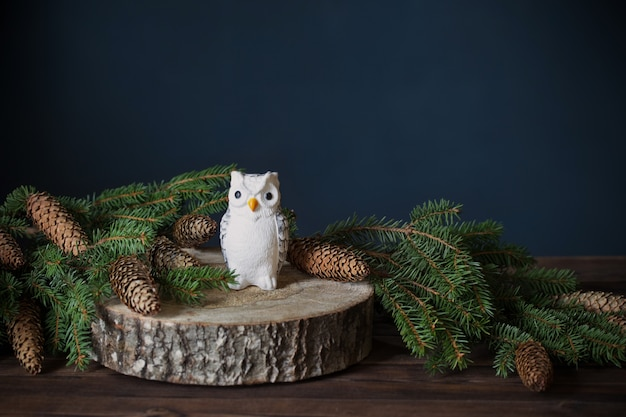 Toy owl on  tree cut with fir  branches