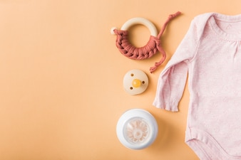 Toy; pacifier; milk bottle and pink baby onesie over an orange background
