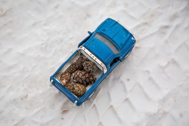 눈 위 실제 자동차의 타이어 트랙에 전나무 콘을 운반하는 겨울 도로의 장난감 픽업 트럭