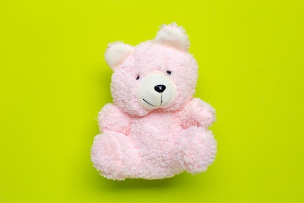 Toy pink bear on green background.