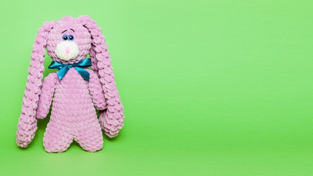 Toy pink bunny or hare with a bow on a green background, space for text