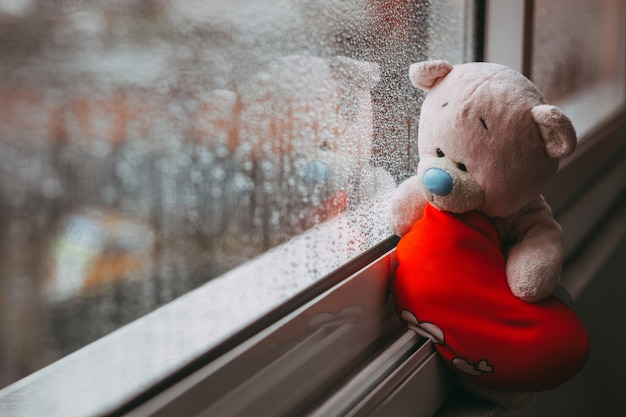 A toy pink sad bear with a red plush heart sitting on the windowsill autumn rainy day raindrops