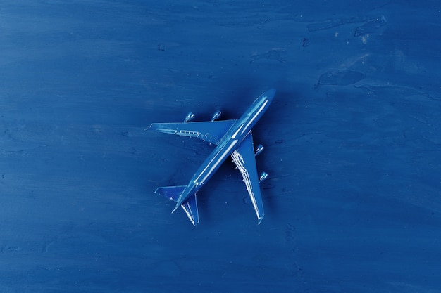 Toy plane on classic blue table, top view