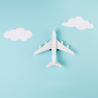 Toy plane and clouds on blue background