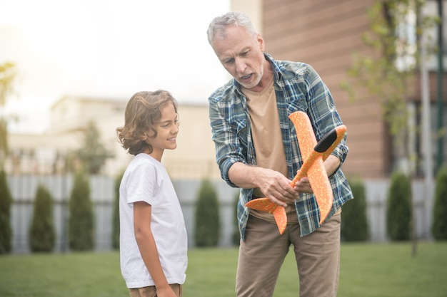 Toy plane. gray-haired dad showing to his son how to use the toy plane