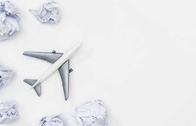 장난감 비행기는 흰 복사 공간에 구름 종이를 통해 날고있다
