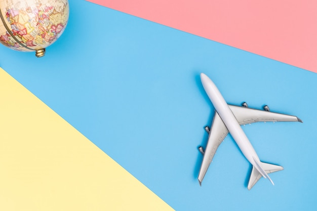 Toy plane is traveling the world concept on blue pink yellow