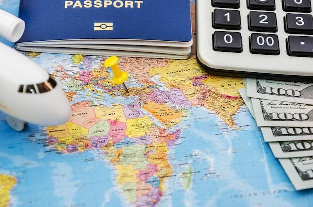 지도 배경에 여권과 달러가 있는 장난감 비행기 모델