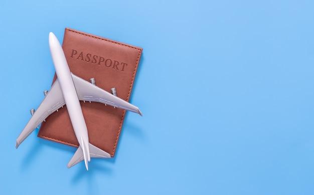파란색 복사 공간에 여권 위에 장난감 비행기