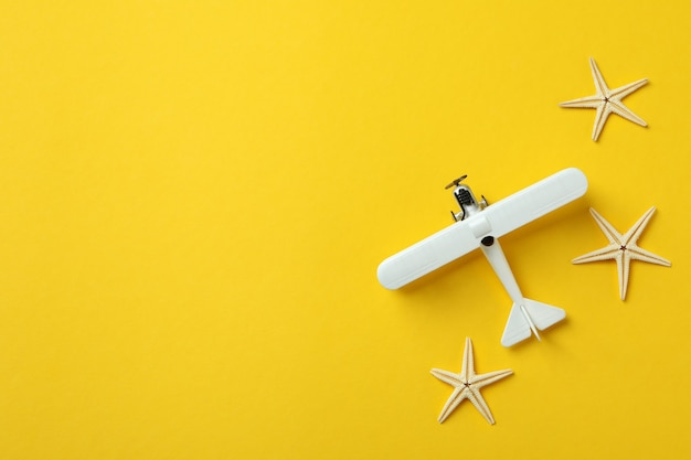 Toy plane and sea stars on yellow background