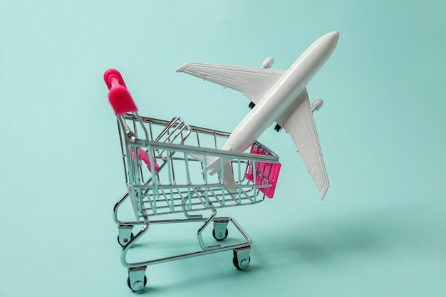 Toy plane and shopping push cart on blue background