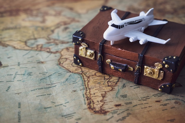 Toy plane and suitcase on vintage map