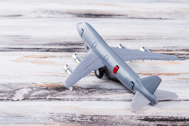 Toy plane on white wood. close up grey model airplane.