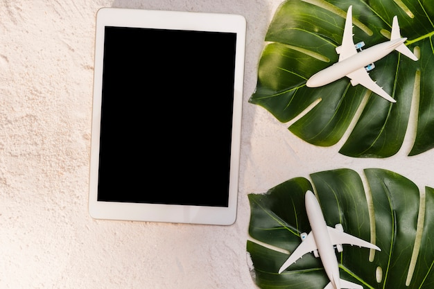 Toy planes on monstera leaves and tablet