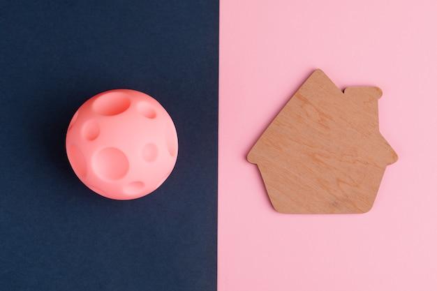 밝은 배경 위에 분화구와 집이있는 장난감 행성, 화성에 저렴한 주택의 개념