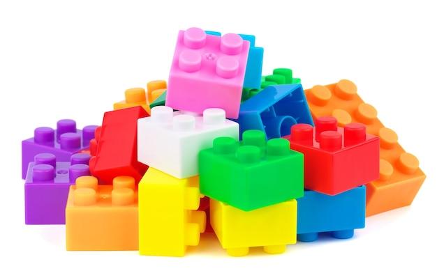 白い背景の上のおもちゃのプラスチックの建物のカラフルなブロック
