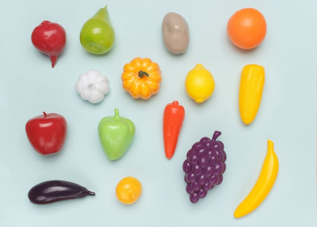 Toy plastic imitations (fake) of different vegetables and fruits on blue