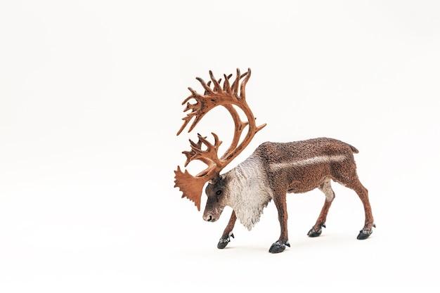 Игрушечный пластиковый олень с рогами на белой поверхности
