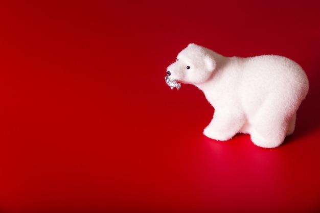 Игрушечный полярный медведь с рыбой во рту на красном фоне. горизонтальное фото
