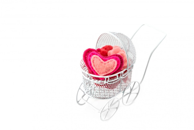 Toy pram with wool heart isolated on white background. valentine's day or newborn greeting card.