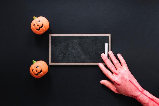 黒板とピンクの手でおもちゃのカボチャ