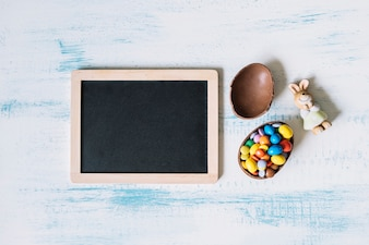 Toy rabbit and chocolate egg near blackboard
