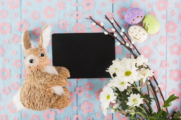 Toy rabbit near paper and easter symbols