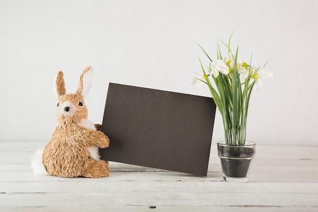 Toy rabbit near snowdrops