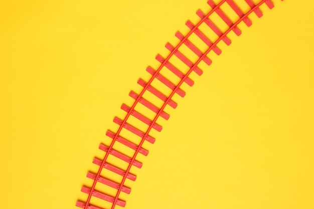 Toy railroad tracks on yellow pastel. top view
