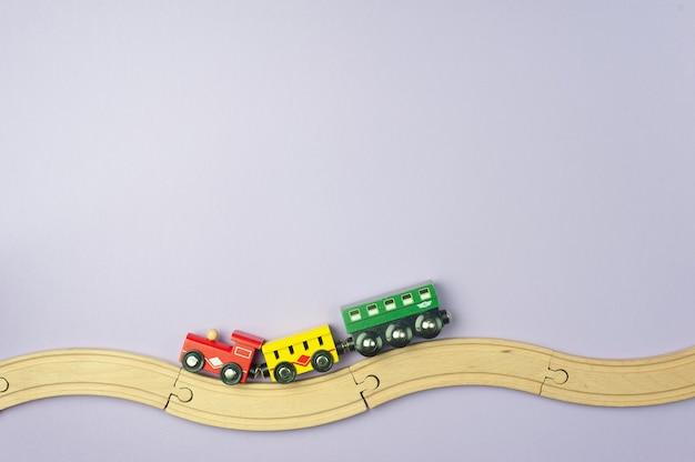 おもちゃの鉄道と紫色の背景に小さな電車。フラットレイ、上面図。テキストの場所