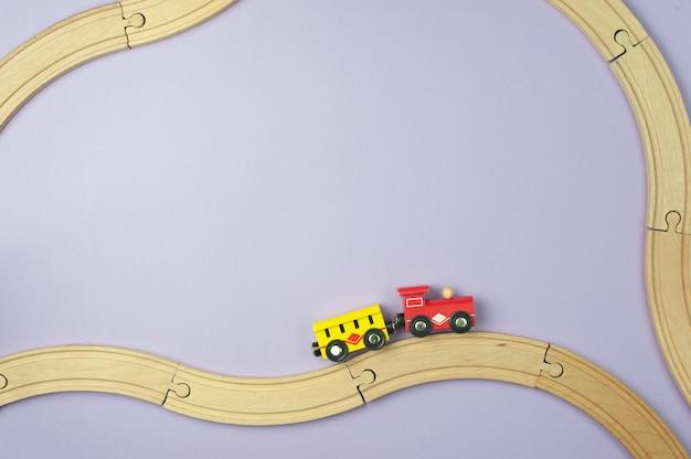 おもちゃの鉄道と紫色の背景に小さな電車。フラットレイ、上面図。旅行のコンセプト