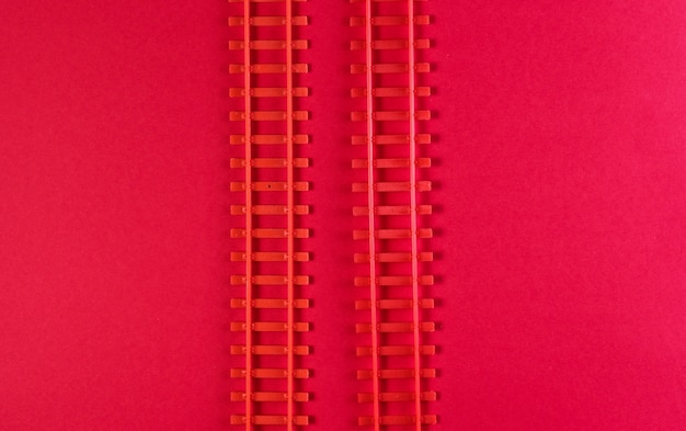 Toy railway rails on a red table.