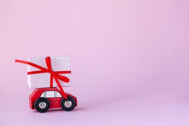 バレンタインデーのコンセプトのためのピンクの壁の屋根にプレゼントボックスが付いているおもちゃの赤い車。