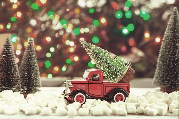 Игрушечный красный автомобиль с елкой в крыше на праздничном фоне